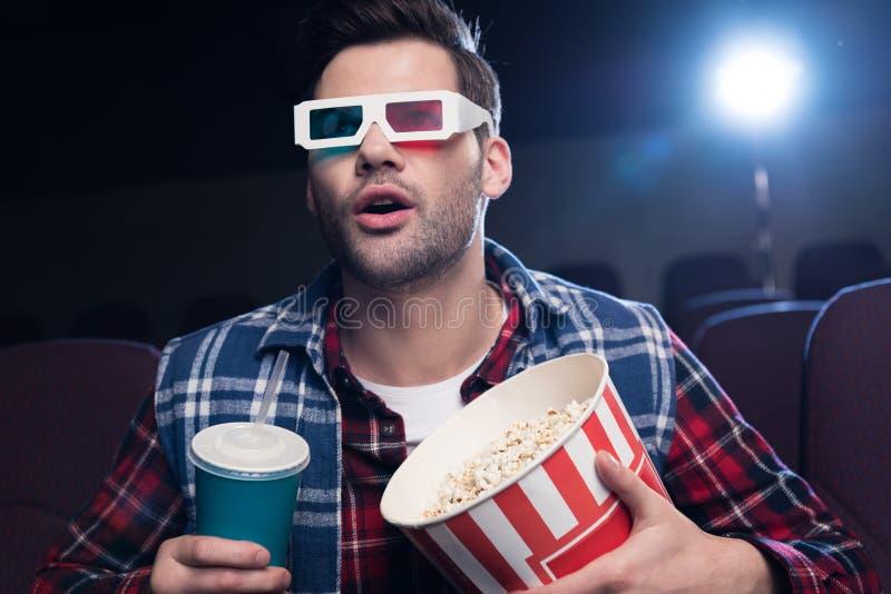 emotionaler gutaussehender Mann in den Gläsern 3d mit Popcorn und aufpassendem Film des Sodas lizenzfreie stockfotos