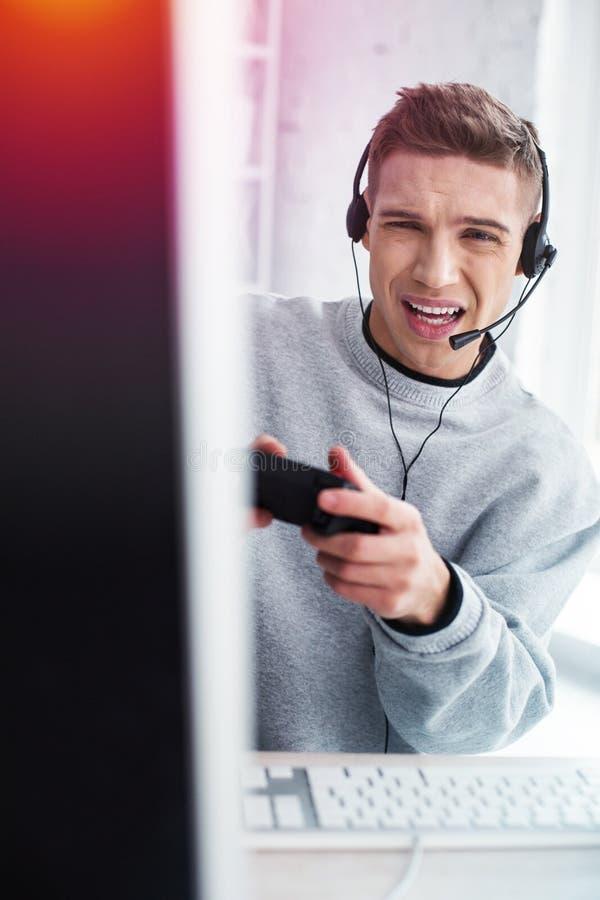 Emotionaler hübscher junger Mann, der während verlierendes Videospiel neugierig sich fühlt stockbilder