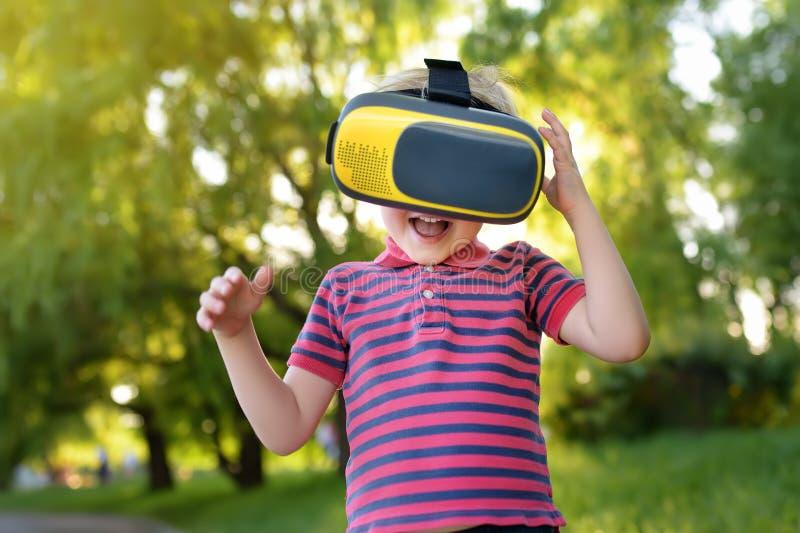 Emotionaler kleiner Junge unter Verwendung des Kopfhörers der virtuellen Realität im Freien r stockbilder