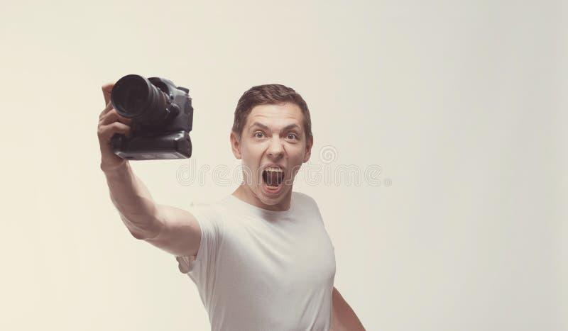 Emotionaler Mann mit der Kamera lokalisiert auf hellem Hintergrund Holdingdigitalkamera des jungen Mannes mit dem schreienden Sie stockfotos
