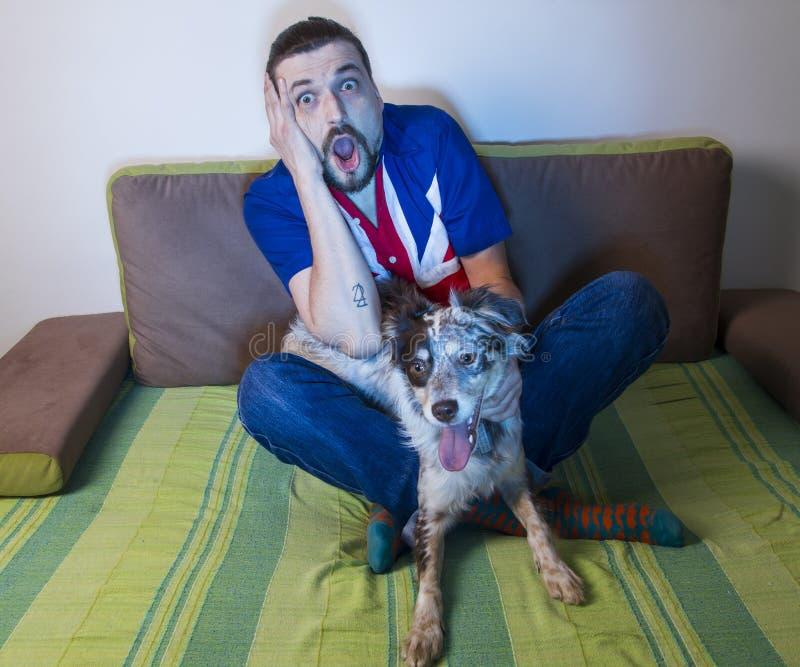 Emotionaler Mannfan, der auf Sofa mit Hund sitzt stockbild