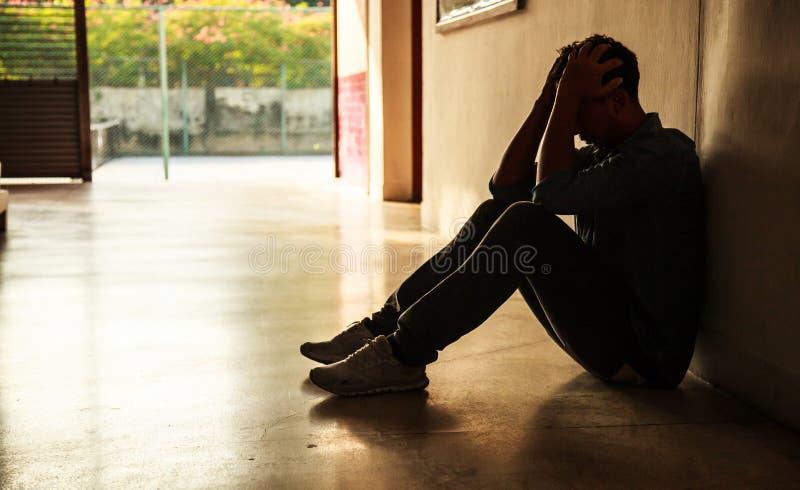 Emotionaler Moment: bemannen Sie das sitzende Halten Haupt in den Händen, der betonte traurige junge Mann, der die Geistesproblem stockbild