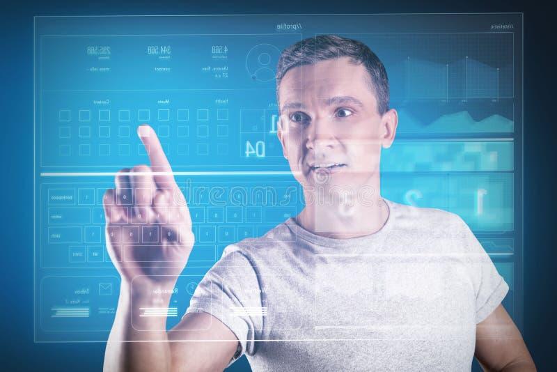 Emotionaler Programmierer, der beim Arbeiten mit seiner neuen Ausrüstung beeindruckt schaut stockbild