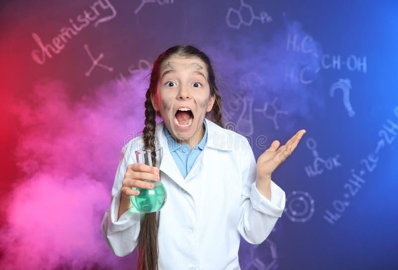 Emotionaler Schüler, der Florenz-Flasche im Rauche gegen Tafel mit Formeln hält lizenzfreie stockfotos