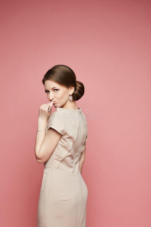 Emotionales brunette vorbildliches Mädchen in einem beige Kleid mit dem stilvollen Schmuck lokalisiert am rosa Hintergrund lizenzfreies stockbild