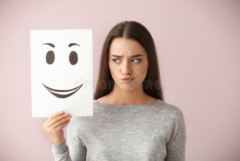 Emotionales Frauenholdingblatt papier mit gezogenem Emoticon auf Farbhintergrund lizenzfreie stockfotos