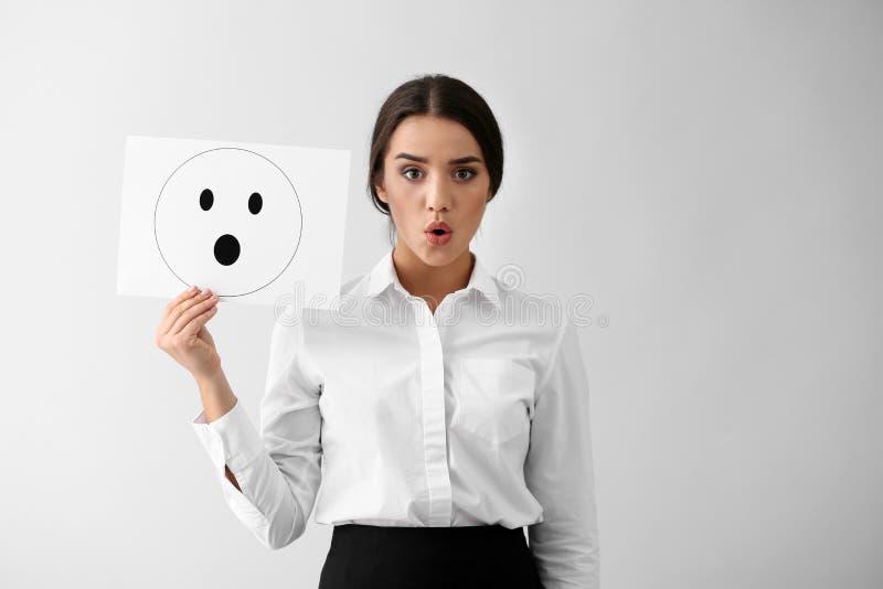 Emotionales Frauenholdingblatt papier mit gezogenem Emoticon auf hellem Hintergrund lizenzfreie stockfotos