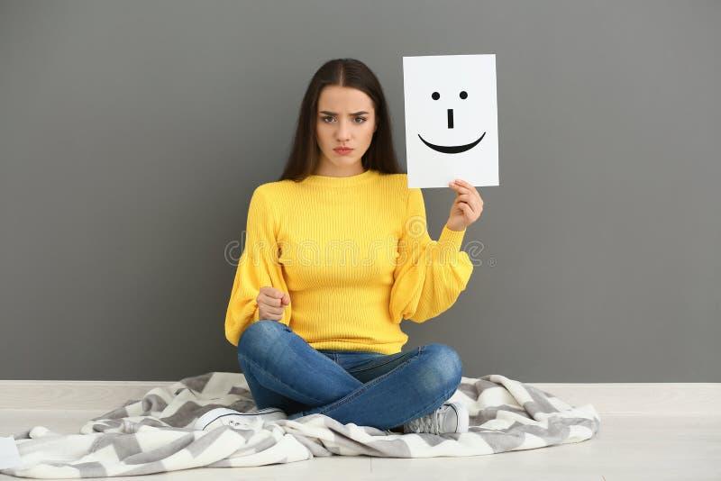 Emotionales Frauenholdingblatt papier mit gezogenem Emoticon beim Sitzen nahe grauer Wand lizenzfreie stockbilder