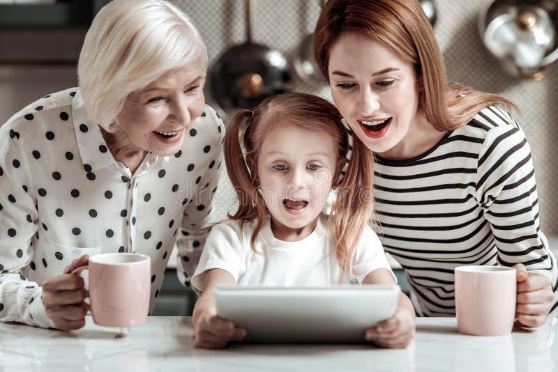 Emotionales Mädchen, das mit ihrer Mutter und Oma sitzt und die Tablette betrachtet lizenzfreies stockbild