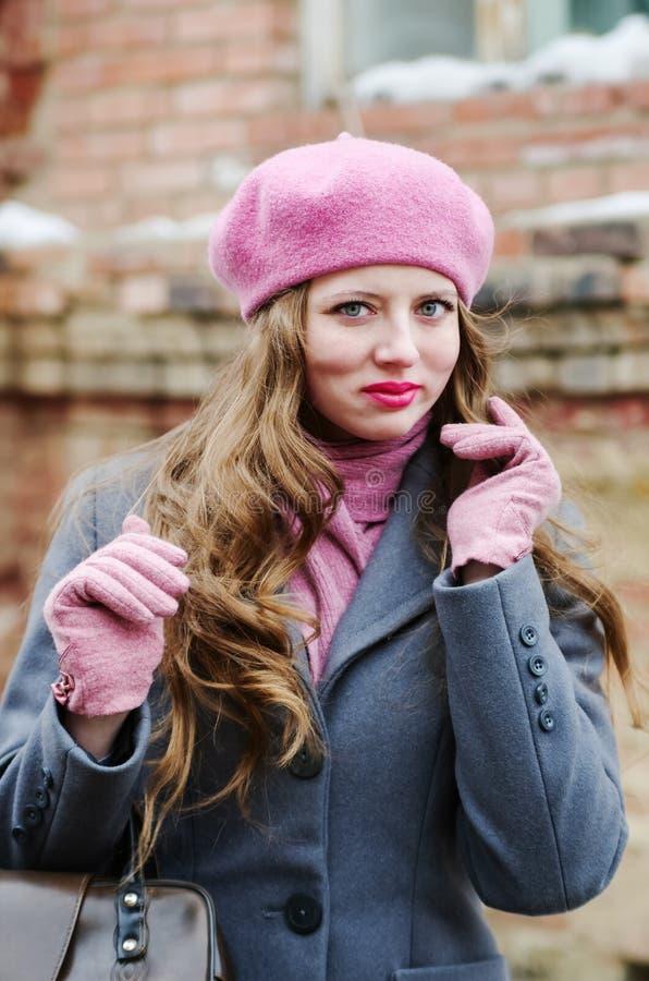 Emotionales Mädchen im grauen Mantel und im rosa Barett stockbild