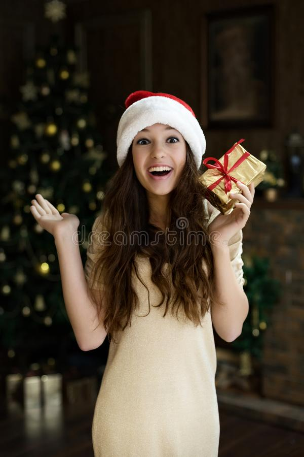 Emotionales Mädchen in Sankt-Hut mit Begeisterung und Freude und Glück hält gegeben zu ihrem neues Jahr ` s Weihnachtsgeschenk stockfoto