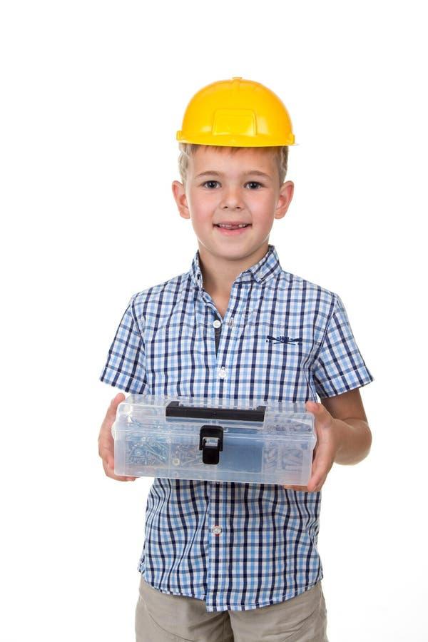 Emotionales Porträt des hübschen Jungen blaues kariertes Hemd und gelben Schutzhelm tragend, den Werkzeugkasten halten, lokalisie stockfotografie