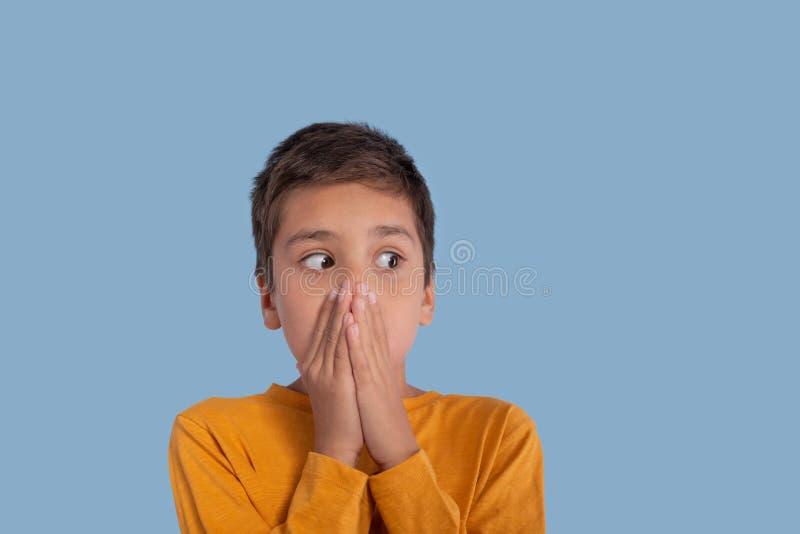 Emotionales Porträt des Jungen, der in einem roten Hemd auf einem blauen b trägt stockbilder