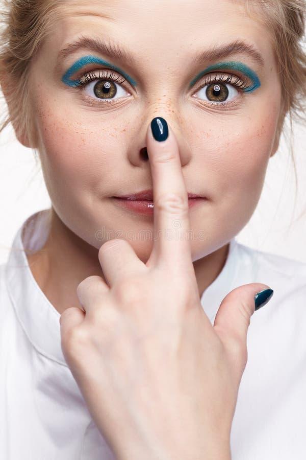 Emotionales Porträt jungen Blondine berührt ihre Nase mit ihrem Finger lizenzfreie stockbilder