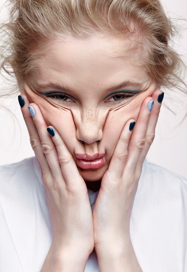 Emotionales Porträt jungen Blondine drückt Gesichtshaut auf Backen zusammen stockbild
