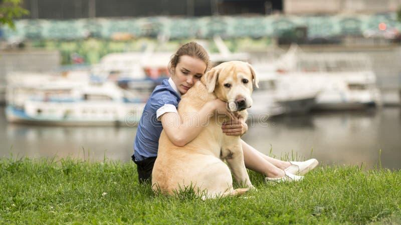 Emotionales Schwarzweiss-Porträt eines traurigen einsamen Mädchens, das ihren Hund umarmt lizenzfreies stockfoto