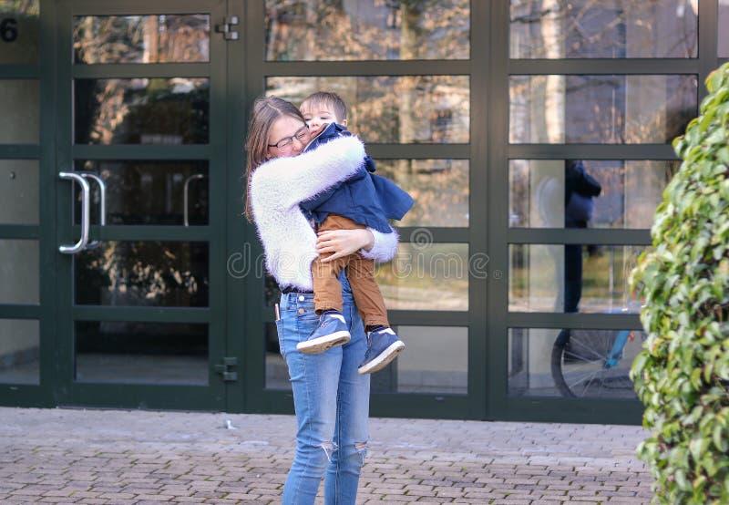 Emotionales Tweenmädchen, das draußen ihren kleinen Babybruder hält und umarmt stockfoto