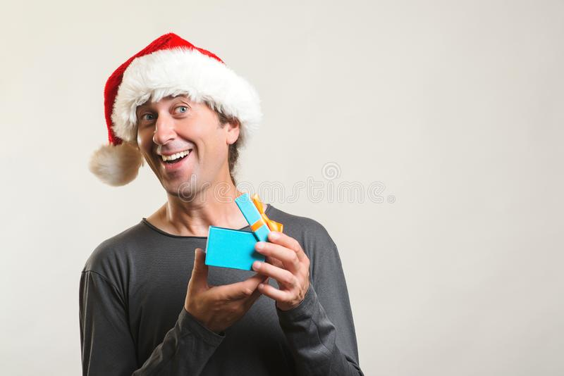 Emotionally happy guy open Christmas gift. Man in Santa hat with gift on white background. Copy space. Christmas shopping and sale stock images