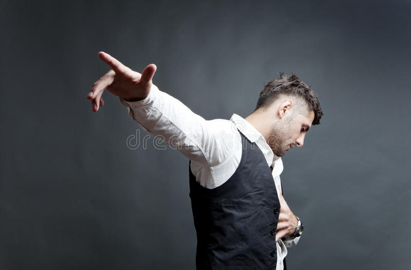 Emotionally hurt young man. With hand on heart gesturing with outstretched hand, studio background royalty free stock photography