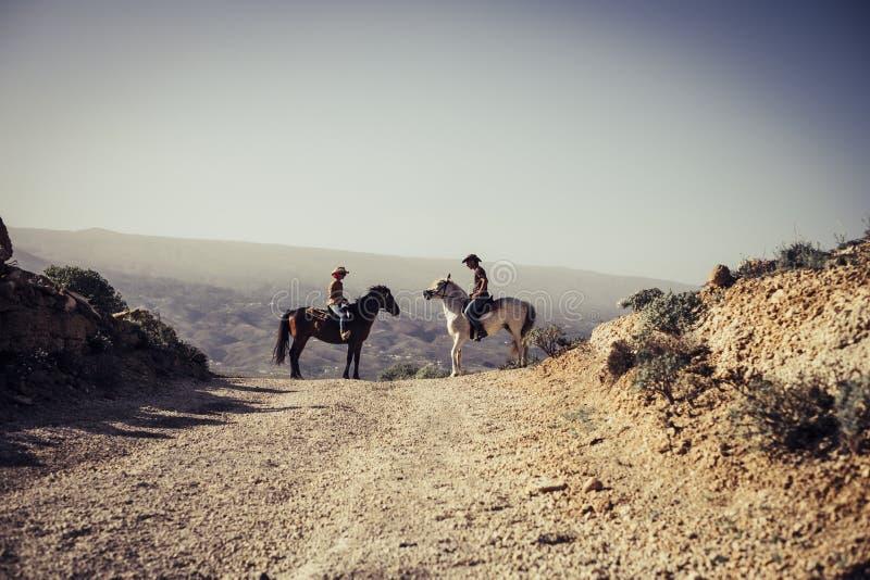 Emotioneel beeld met twee paarden en een coulpe die in de aard berijden stock fotografie