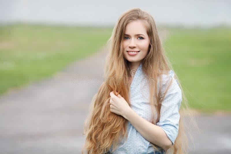 Emotioneel dicht omhooggaand portret van een volwassen mooie blondevrouw met het schitterende buitengewoon lange haar stellen in  stock foto