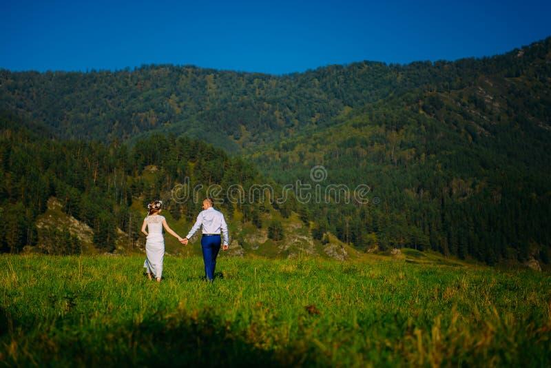 Emotioneel die huwelijk van het gelukkige paar wordt geschoten die van het glamourjonggehuwde op weide in wilde aard lopen Mooie  stock afbeeldingen