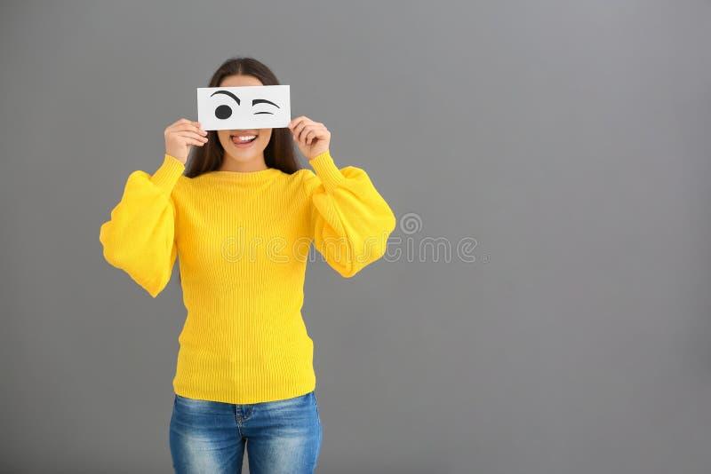 Emotioneel jong vrouwen verbergend gezicht achter blad van document met getrokken ogen op grijze achtergrond stock afbeeldingen