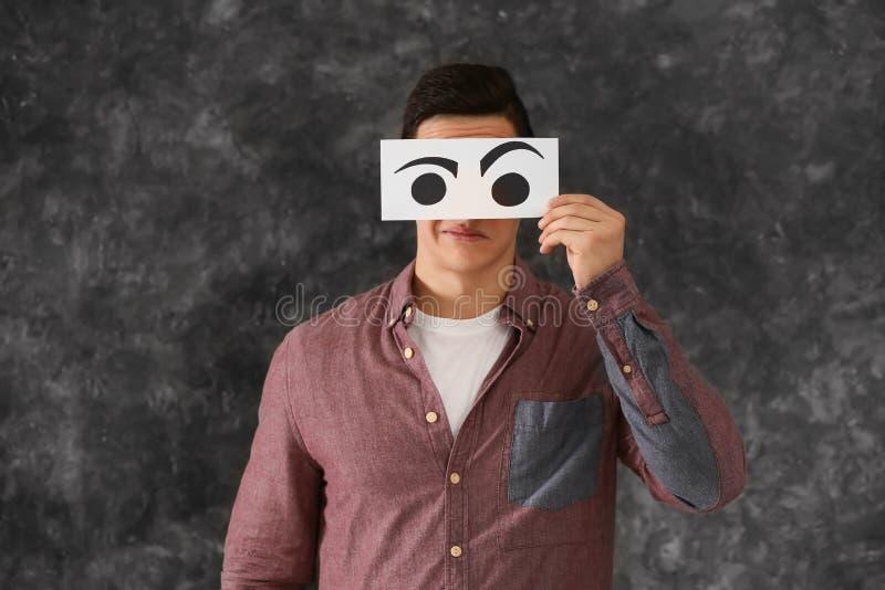Emotioneel jonge mensen verbergend gezicht achter blad van document met getrokken ogen op grijze achtergrond stock foto
