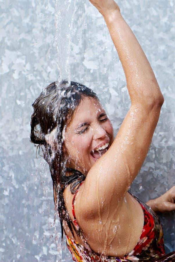 Emotioneel Latijns meisje onder een waterstroom stock foto