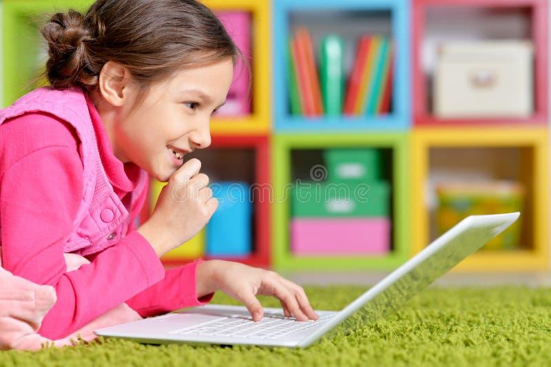 Emotioneel leuk meisje die laptop met behulp van terwijl het liggen op vloer royalty-vrije stock afbeelding