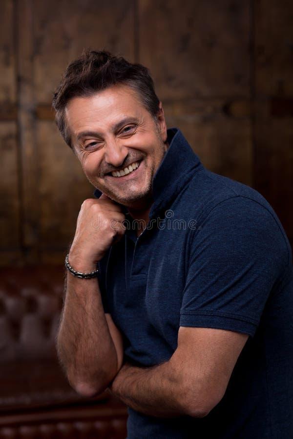 Emotioneel mannelijk model die en zijn hand glimlachen zetten aan het gezicht Portret van de gelukkige man wat betreft zijn kin t stock afbeeldingen