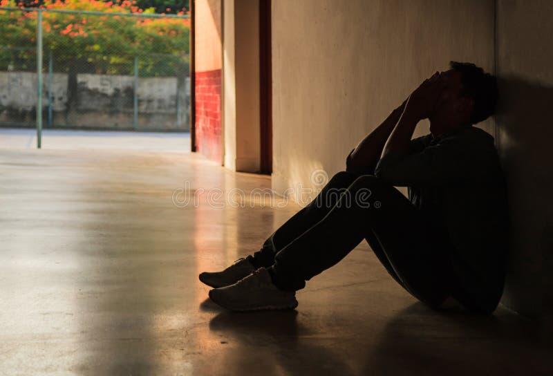 Emotioneel ogenblik: de holdingsgezicht van de mensenzitting in handen, beklemtoond droevig jong mannetje die geestelijke gedepri stock afbeelding