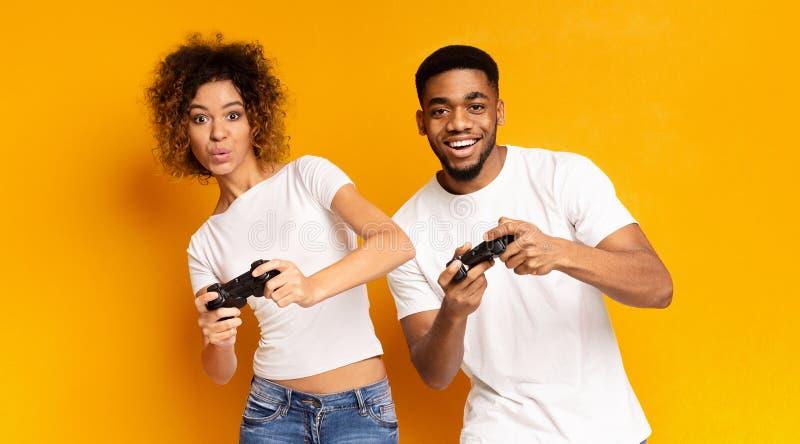 Emotioneel paar het spelen videospelletje met bedieningshendels stock afbeeldingen