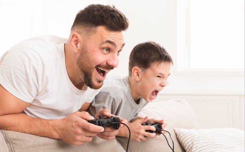 Emotioneel papa en zoons het spelen videospelletje die thuis, voor winst concurreren stock afbeelding