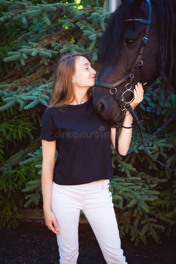 Emotioneel Portret van een wijfje in liefde met paarden, zwart Friesian hengst volbloed- huisdier royalty-vrije stock fotografie