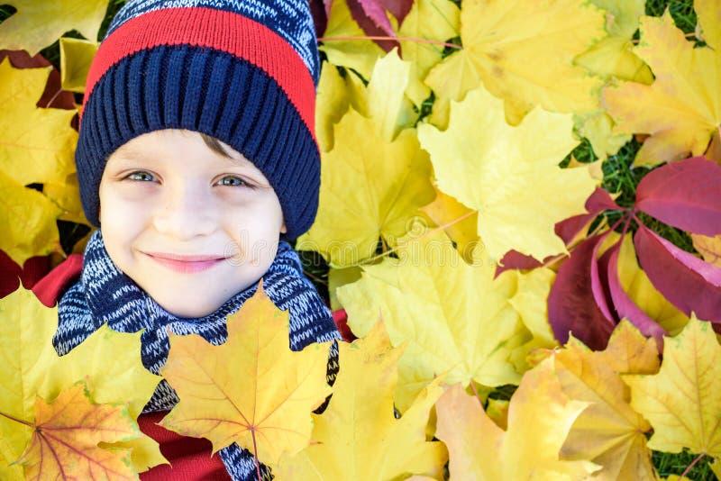Emotioneel portret van gelukkig en actief weinig jongen die de camera met een glimlach bekijken die op zijn rug op een tapijt van stock foto's