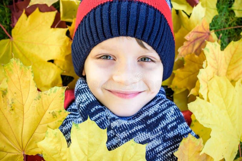 Emotioneel portret van gelukkig en actief weinig jongen die de camera met een glimlach bekijken die op zijn rug op een tapijt van royalty-vrije stock fotografie