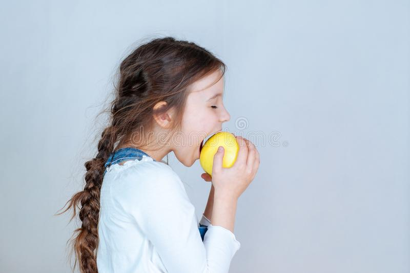 Emotioneel portret weinig mooi meisje die met vlechten in jeansoverall beten eten die een appel houden 6-7 jaar studio stock foto