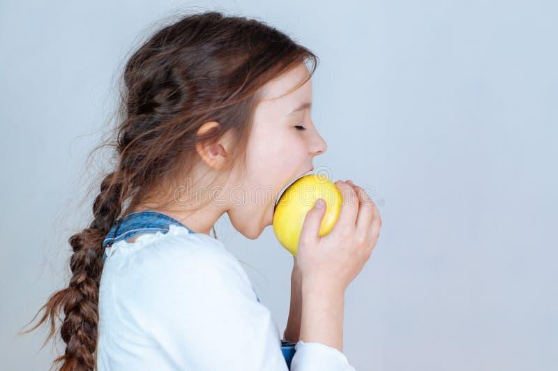 Emotioneel portret weinig mooi meisje die met vlechten in jeansoverall beten eten die een appel houden 6-7 jaar studio royalty-vrije stock foto
