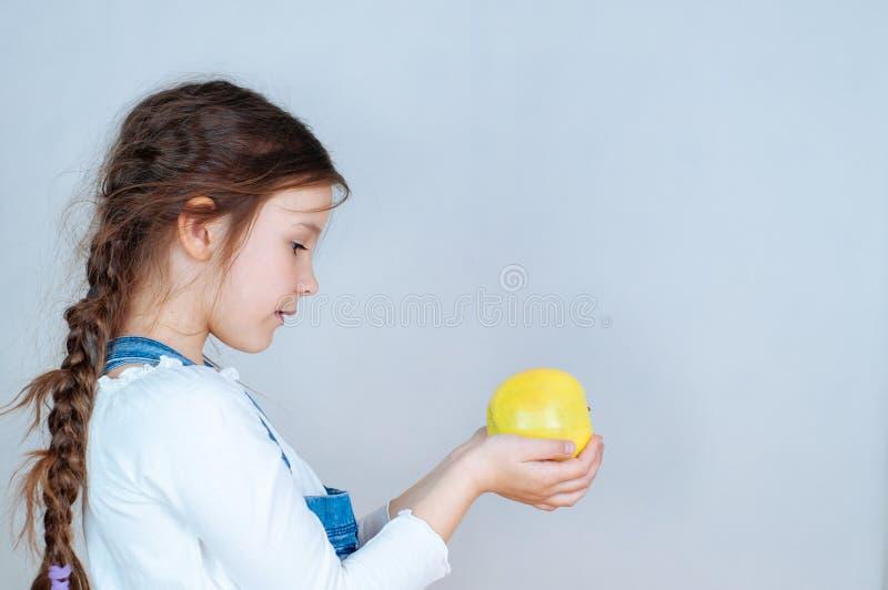 Emotioneel portret weinig mooi meisje die met vlechten in jeansoverall beten eten die een appel houden 6-7 jaar studio royalty-vrije stock afbeelding
