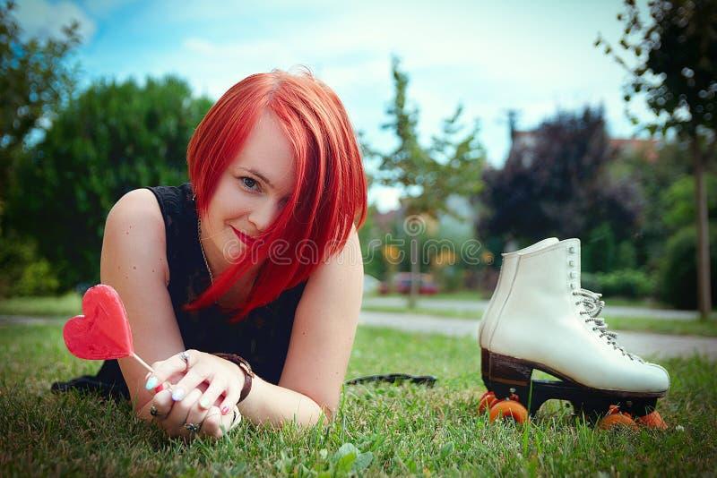 Emotioneel roodharig meisje in een zwarte kleding die op graswi liggen royalty-vrije stock foto