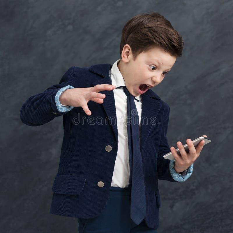 Emotioneel weinig jongen die bij smartphone gillen royalty-vrije stock afbeelding