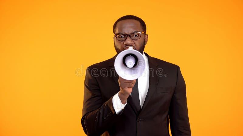 Emotionele Afrikaans-Amerikaanse manager die aan luidspreker, discipline, uiterste termijn schreeuwen stock fotografie