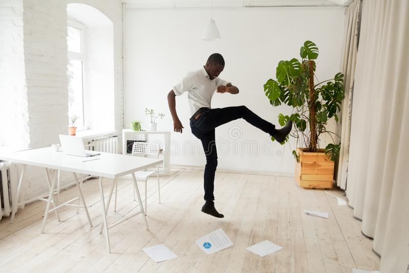 Emotionele beklemtoonde Afrikaans-Amerikaanse zakenman die scattere schoppen stock foto's