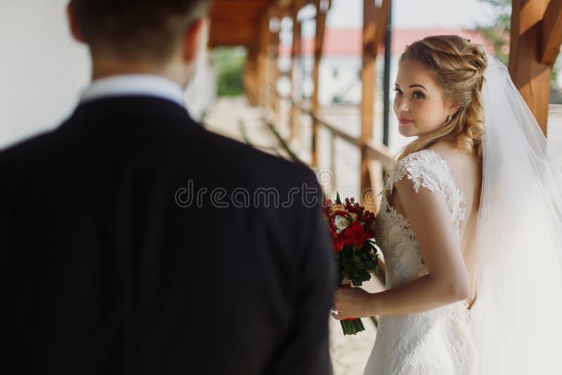 Emotionele blondebruid die & bruidegom, elegante bruid glimlachen bekijken royalty-vrije stock foto