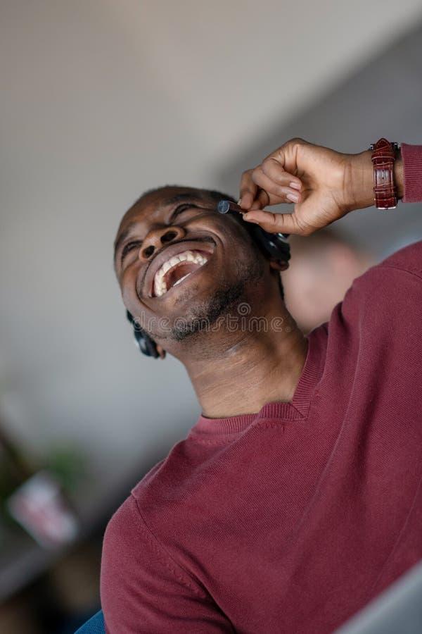Emotionele donkere gevilde mannelijke freelancer die voltooid project met succes vieren royalty-vrije stock fotografie