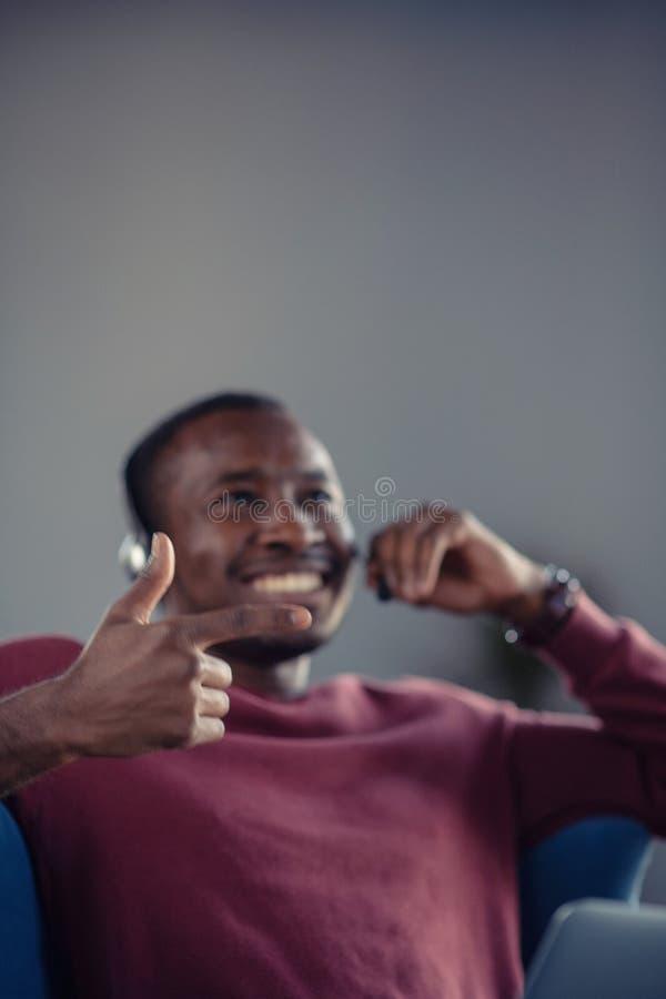 Emotionele donkere gevilde mannelijke freelancer die voltooid project met succes vieren stock afbeelding