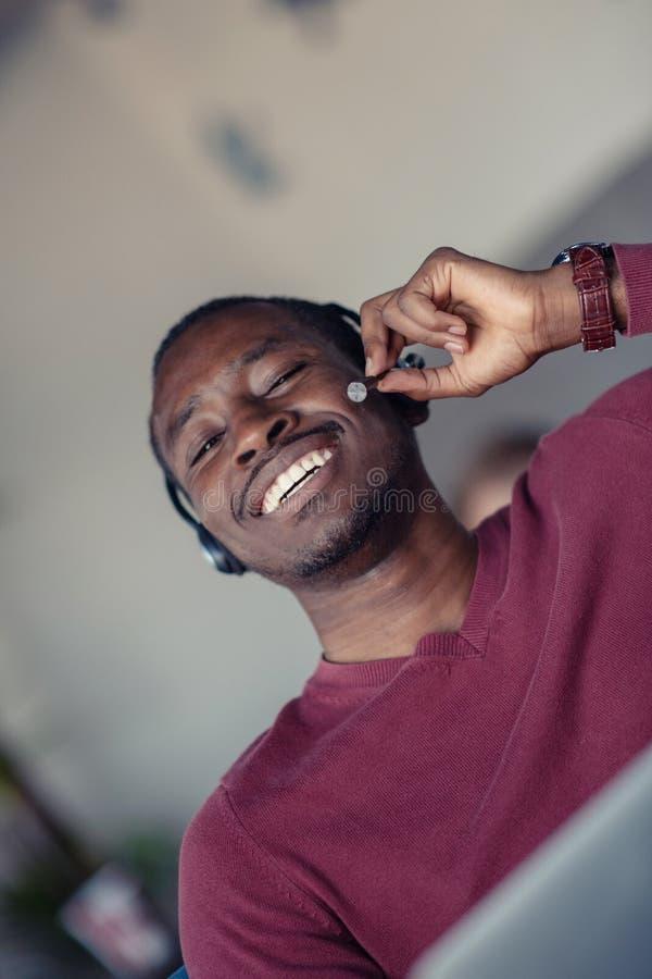 Emotionele donkere gevilde mannelijke freelancer die voltooid project met succes vieren stock afbeeldingen