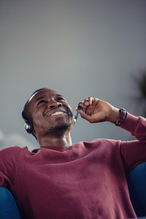 Emotionele donkere gevilde mannelijke freelancer die voltooid project met succes vieren royalty-vrije stock afbeelding