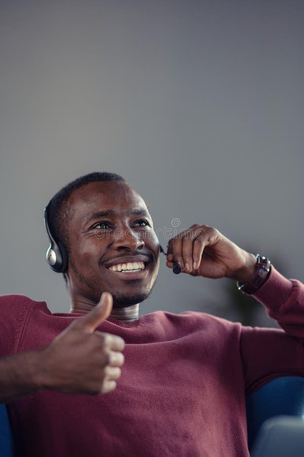 Emotionele donkere gevilde mannelijke freelancer die voltooid project met succes vieren stock foto